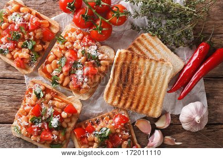 Toasts With Beans In A Tomato Sauce, Cheese And Herbs Closeup. Horizontal Top View
