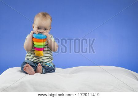 Adorable little baby boy, sitting on the white blanket with a toy in hands , studio shot, isolated on blue background.