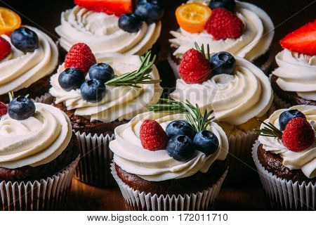 Fresh tasty chocolate cupcakes with berries. Selective focus. Dark wooden background.Rustic style, place for text.