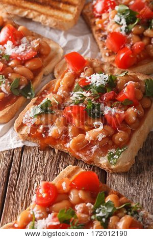 Toasts With Beans In A Tomato Sauce, Cheese And Herbs Closeup. Vertical