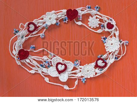 Handmade crocheted cotton organic lace wreath. White knitted frame pattern handicraft background needlework creative craft. Tender crochet wreath with flowers hearts beads place for text