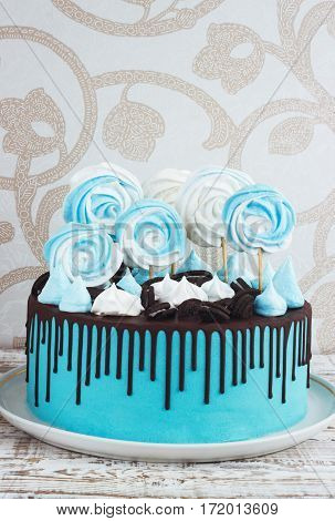 Children's blue cake rainbow color on a white background with wood meringue