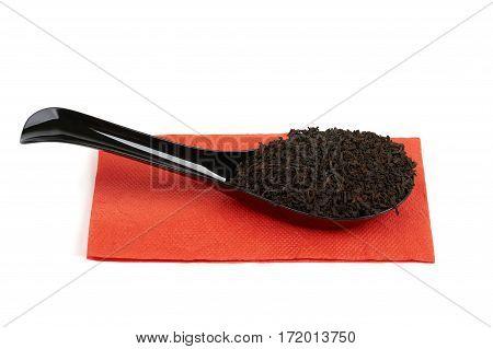 Black plastic spoon full of black tea on red paper napkin isolated on white