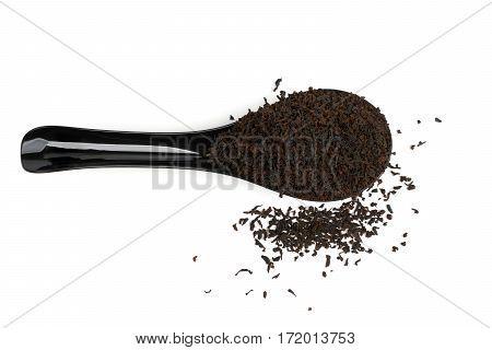 Black plastic spoon full of black tea isolated on white. Upper view.