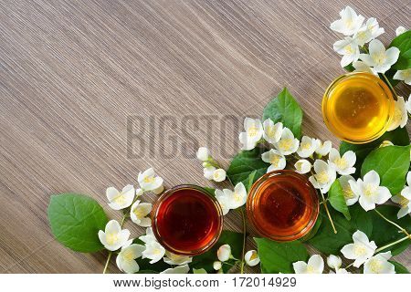 Three bowls of honey and branch blooming jasmine on a wooden background. Free space for text