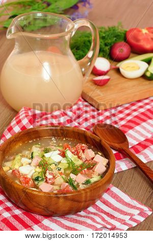 Okroshka. Cold summer soup of vegetables in a wooden bowl. Homemade kvass in a glass jug and vegetables on a cutting board