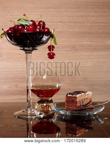 Cherries brandy and a piece of chocolate cake