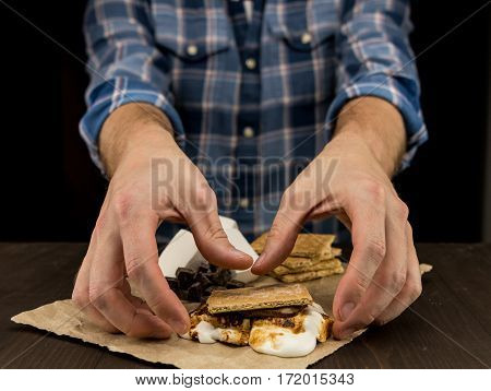Mans Arms Reach Out for Smore with toasted marshmallows poster