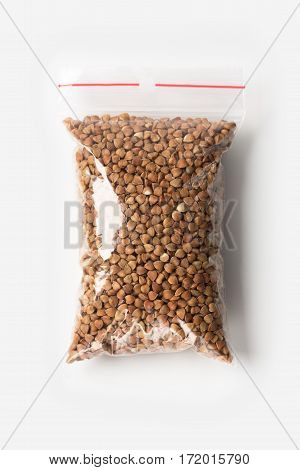 Plastic Transparent Zipper Bag With Full Of Premium Buckwheat Groats Isolated On White, Vacuum Packa