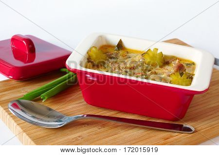 Meat stew with pickles. In red ceramic stewpot . Stands on a cutting board.near  spoon