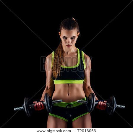 Young Athletic Woman In Sportswear With Dumbbells In Studio Against Black Background. Ideal Female S