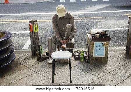 Japanese Older People Serviced Repair Shoes On Pathway Beside Traffic Road For People Use At Shinjuk