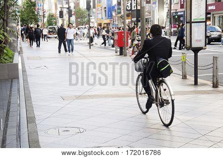 Japanese people walking crosswalk traffic road and biking bicycle on pathway beside traffic road at Shinjuku city on October 20 2016 in Tokyo Japan