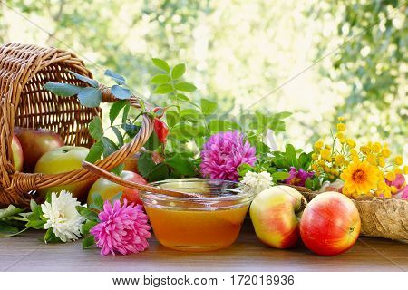 Flower honey apples and garden flowers. Apples crumbled from the basket. Floral honey and garden flowers