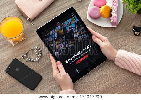 Alushta Russia - November 17 2016: Woman holding iPad Pro Space Gray with multinational entertainment company Netflix provides streaming media and video on the screen.