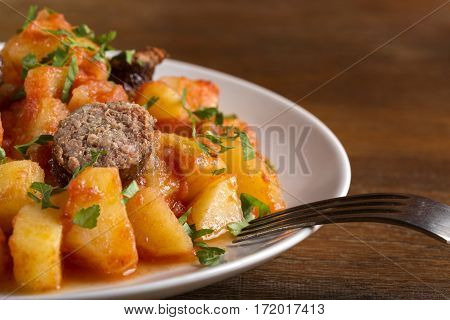 Potatoes stew with pork sausage and herbs on plate over wooden background