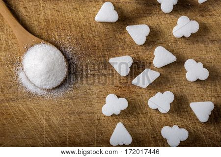 Different sugar cubes shapes and one wooden spoon filled with sugar on wood background