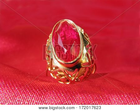 gold ring with a natural large ruby gem crystal on red satin background