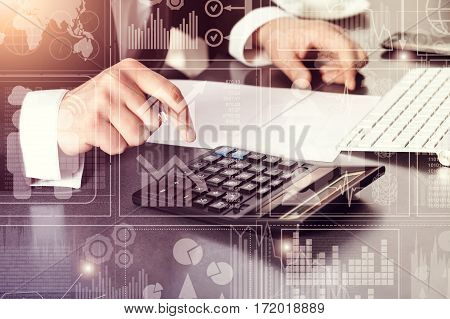 Businessman in office business chart sitting by computer and finds calculator