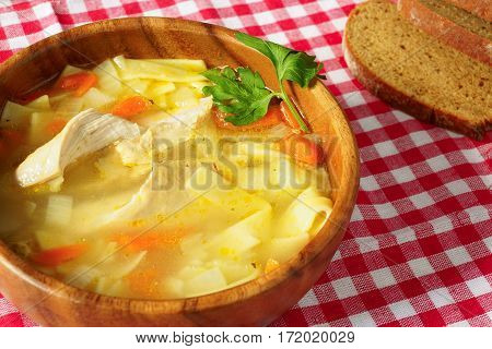 Chicken with noodles soup in a wooden bowl on a red tablecloth with dark bread.
