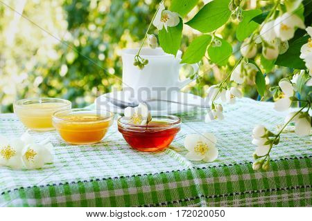 Three bowls of honey and cup of tea on the table under the jasmine bush.