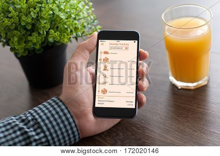 man hand holding phone with app tracking delivery package on desk office
