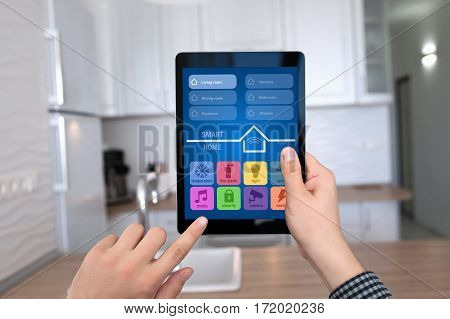 male hands holding tablet with app smart home on background kitchen in house