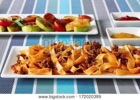 Pasta with minced meat on a white plate. Grilled vegetables on the second plate. Mustard and ketchup in a gravy boat.
