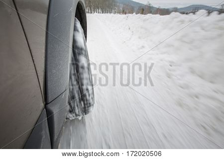 Car with winter tires on a slippery, snowy road - motion blur techinque used to convey movement, speed of the car