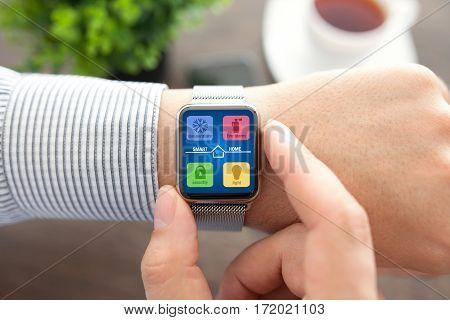 Man hands with smart watch app smart home on screen