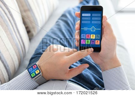 man lying on sofa holding watch and phone with app smart home on screen