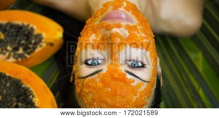 Beautiful caucasian Woman Having fresh Papaya natural facial mask apply. Papaya Peeling. Skin care and Wellness (outdoors). Facial vitamin mask of papaya slices at spa salon. Antioxidant cosmetic