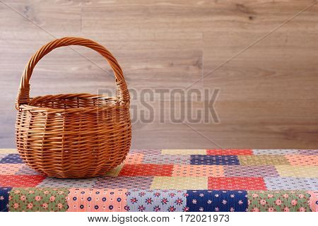Empty wicker basket on the table with colorful tablecloth. Rustic style.