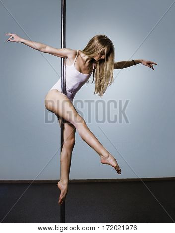 Young sexy pole dance woman. Performance on pole