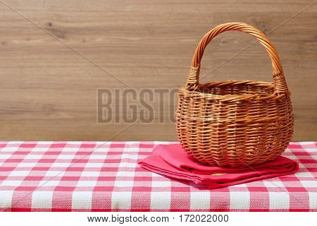An empty wicker basket on a red checkered tablecloth. Wooden background. Rustic style. Free space for creativity.