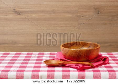 Empty wooden bowl and spoon on a red checkered tablecloth. Wooden background. Rustic style. Free space for creativity.