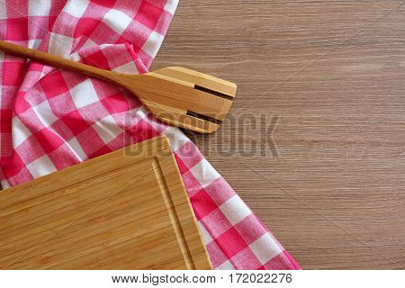 Checkered tablecloth wooden spoon and a chopping board on a wooden table. Top view