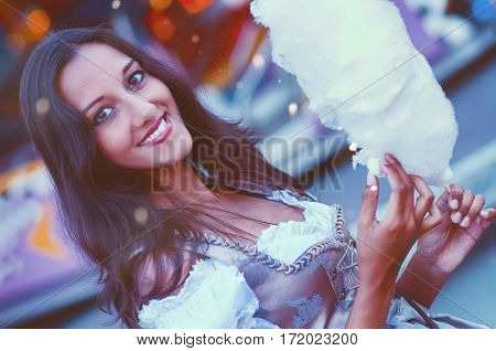 Gorgeous brunette in traditional Bavarian clothing holding cotton candy at carnival