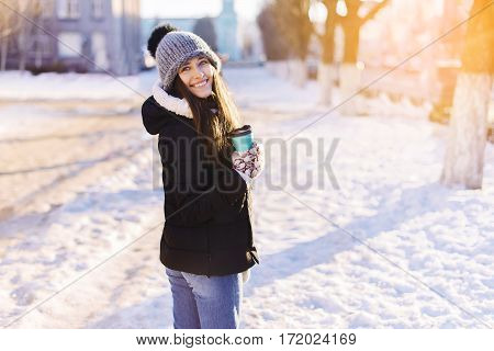 Young Beautiful Woman Is Drinking Coffee Outdoors At Winter Street Background.