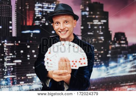Magician showing trick with playing cards. Magic circus gambling
