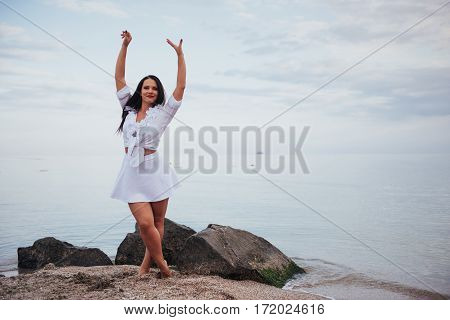 girl in frock dances barefoot on sand beach hands above against azure sea wind shakes long hair