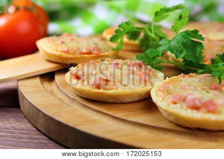 small pizza with cheese,ham and  fresh herbs