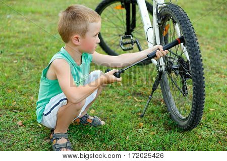 Young boy pumping the bicycle tube on meadow
