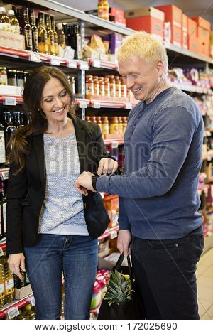 Happy Couple Using Smart Watch In Grocery Store