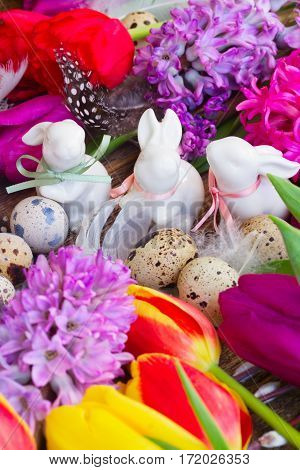 Spring fresh flowers with easter eggs and three white pocelane rabbits