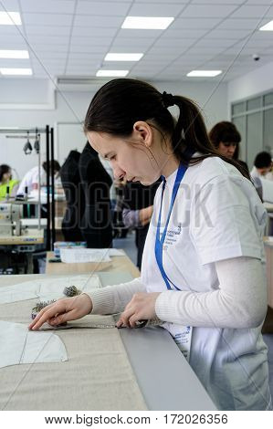 Tyumen Russia - February 17. 2017: Open championship of professional skill among youth World skills Russia Tyumen - 2017. Tailor measuring necessary amount of material for sewing cloth