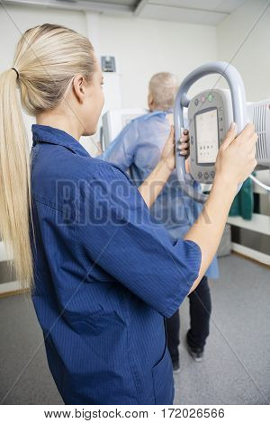 Female Professional Taking Xray Of Patient