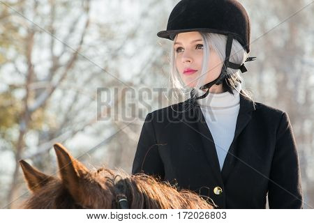 Portrait of young girl jockey riding a horse in a winter forest