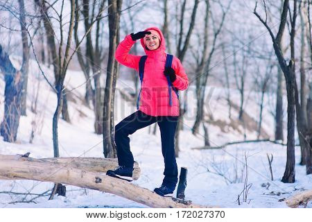 Woman Hiker Walking Up On Snowy Winter Forest Slope With Backpack