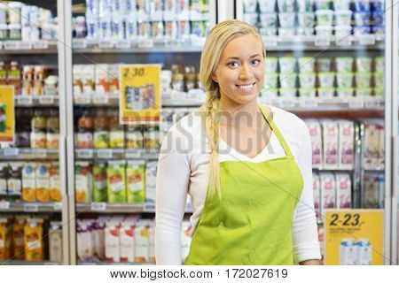 Confident Female Worker Smiling In Grocery Store